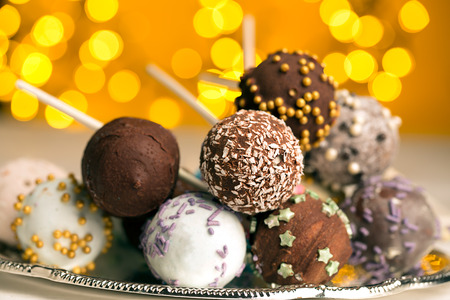 47984557 - colorful cake pops on the blurred yellow bokeh background